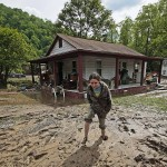 A young girl picks her way through mud following flooding in Mingo County, W.Va., in May. (Steven W. Rotsch/West Virginia Governor's Office)